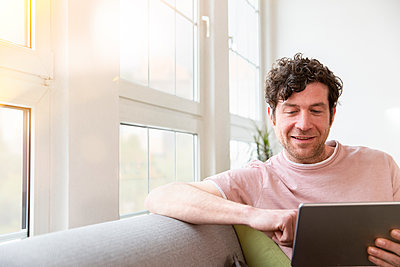 Man sitting on couch at home using tablet - p300m2188571 by Florian Küttler