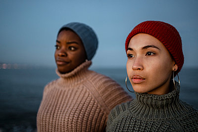 Female friends wearing knit hat looking away while standing against sky - p300m2243467 by Rafa Cortés