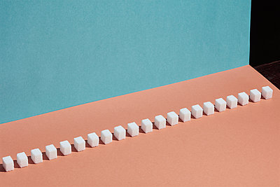 Sugar cubes in a row on peach background - p301m2016384 by Larry Washburn