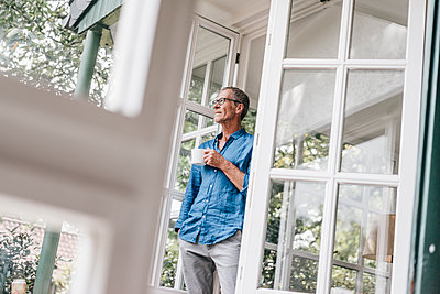 Mature man with cup of coffee looking out of the window - p586m1178510 by Kniel Synnatzschke