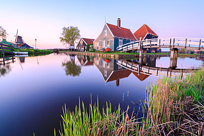Wood houses and windmill reflected in the blue River Zaan at sunset, Zaanse Schans, North Holland, The Netherlands, Europe - p871m1478771 by Roberto Moiola