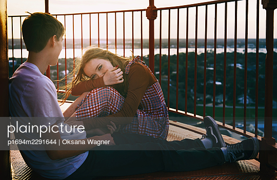 Young couple in love sitting at the viewpoint outdoors against the red metal fence  - p1694m2291644 by Oksana Wagner
