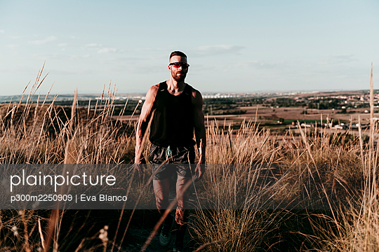 Male sportsperson walking in dried grass against sky during sunset - p300m2250909 by Eva Blanco