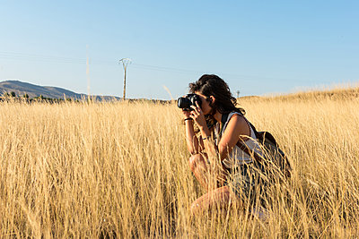 Young woman is taking a picture with a camera in a meadow at sun - p1166m2129527 by Cavan Images