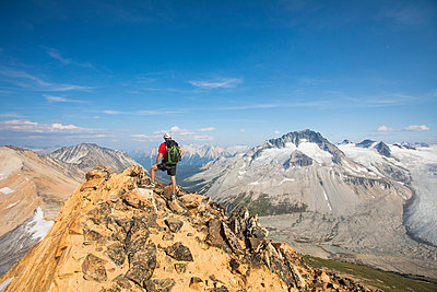 Backpacker standing on mountain summit. - p1166m2153476 by Cavan Images