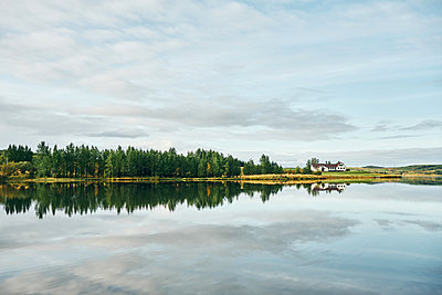 Beautiful landscape of green copse and house on lake shore - p1166m2157260 by Cavan Images