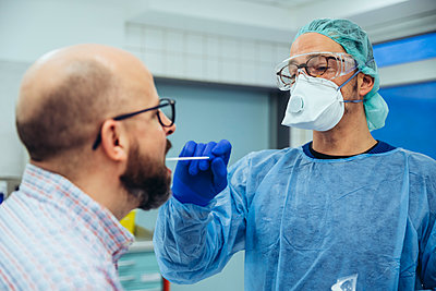 Doctor in hospital taking a swab from patient's mouth - p300m2180402 by Mareen Fischinger