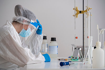 Tired scientist in protective wear sitting at desk - p300m2189153 by SERGIO NIEVAS