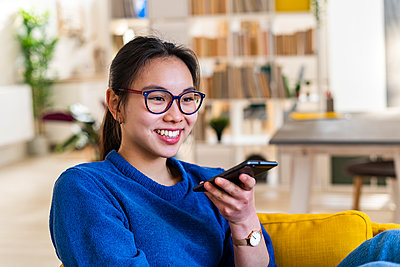 Smiling woman talking on smart phone at home - p300m2265584 by Giorgio Fochesato