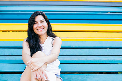 Beautiful woman sitting on multi colored steps - p300m2281304 by Andrés Benitez