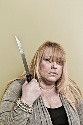 Middle-age blond woman holding a knife - p3971144 by Peter Glass