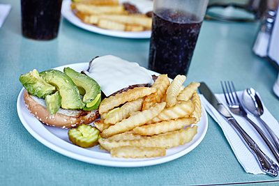 Burger and chips with cola on cafe table, New York City, USA - p429m1408077 by Maria Fuchs