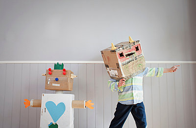Boy with box covering head and homemade toy robot - p429m803092f by Ian Nolan