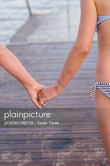 holding hands on a jetty - p1323m1582723 von Sarah Toure