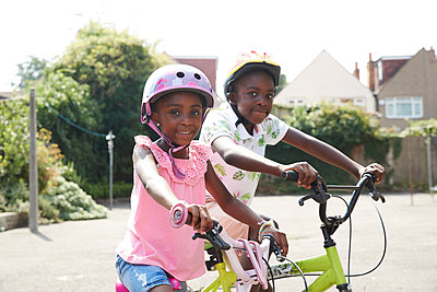 Portrait happy brother and sister riding bikes in sunny neighborhood - p1023m2238486 by Himalayan Pics