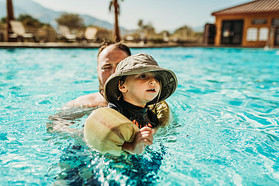 Close up of young toddler boy and father swimming in pool on vacation - p1166m2218231 by Cavan Images