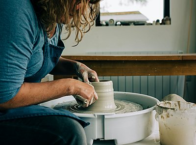 woman modelling clay on a pottery wheel in a studio in the UK - p1166m2285741 by Cavan Images