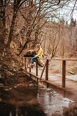 Woman sits on a wooden bridge - p1455m2081770 by Ingmar Wein