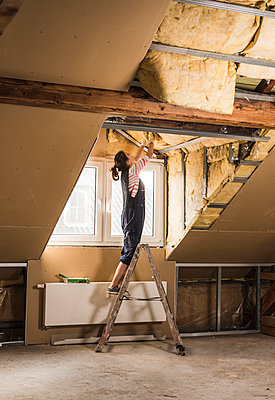Young woman mounting insulation in her new home - p300m1356587 by Uwe Umstätter