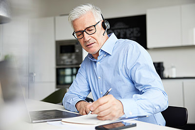 Male professional with wireless headset writing in book at office - p300m2282788 by Rainer Berg