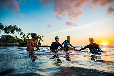 Surfers gliding in sea at sunset, Pagudpud, Ilocos Norte, Philippines - p429m2091583 by dotdotred