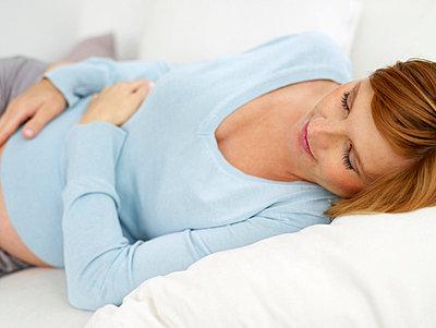 Schwangere Frau schlaeft auf dem Sofa  - p6430110 von senior images