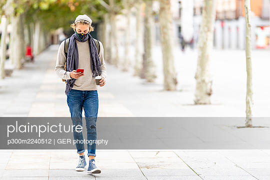 Man wearing face mask using mobile phone while walking on footpath - p300m2240512 by GER photography