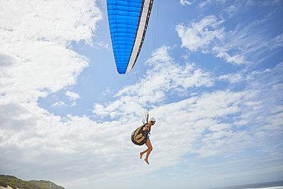 Female paraglider paragliding against sunny blue sky - p1023m2010015 by Trevor Adeline