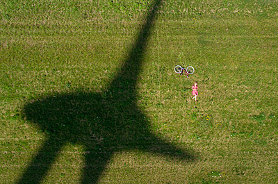Girl resting with the shadow of a wind turbine - p1132m1591232 by Mischa Keijser