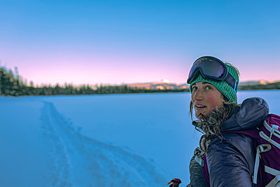 Side view of female skier looking away against clear sky - p1166m1229516 by Cavan Images
