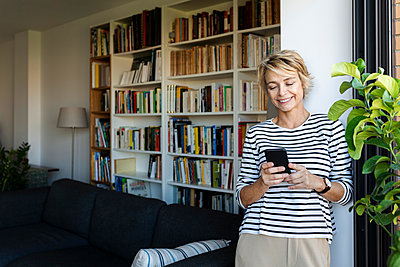 Smiling mature woman standing at the window in living room at home using smartphone - p300m2144804 by Valentina Barreto