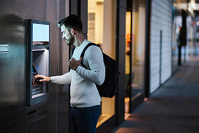 Man withdrawing money at an ATM in the city - p300m2170480 by DREAMSTOCK1982