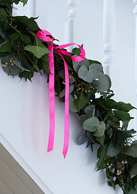 Detail of fresh foliage garland on staircase with pink ribbon bow - p349m2167877 by Sussie Bell