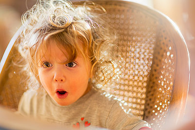 Caucasian baby boy gasping in wicker chair - p555m1413398 by Marc Romanelli