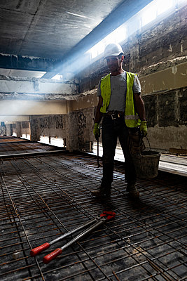 Worker carrying his equipment on a renovation site - p590m2031571 by Philippe Dureuil