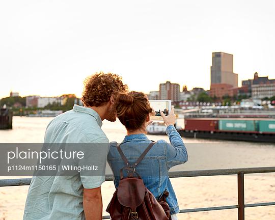 Paar mach Foto mit Tablet von Hamburg Panorama - p1124m1150165 von Willing-Holtz