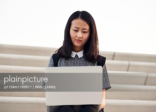Asiatin sitzt mit Laptop auf Treppe - p1124m1169911 von Willing-Holtz