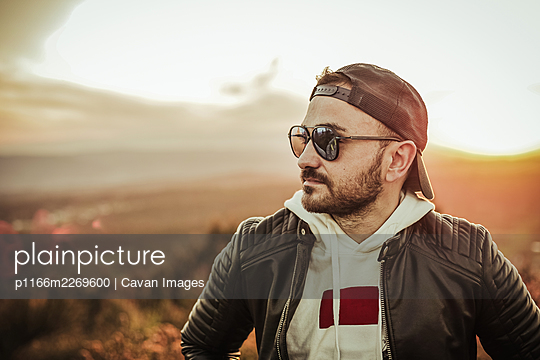Modern guy wearing sunglasses cap and black windbreaker at sunset - p1166m2269600 by Cavan Images