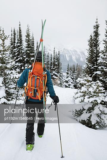 plainpicture | Photo library for authentic images - plainpicture p1192m1546545 - Male skier hiking in snow - plainpicture/Hero Images