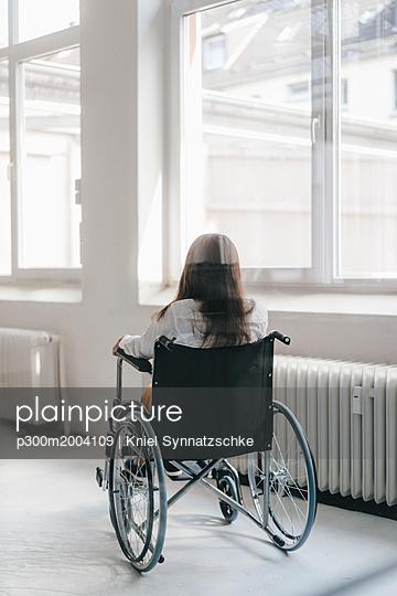 Young handicapped woman sitting in wheelchair, rear view - p300m2004109 von Kniel Synnatzschke