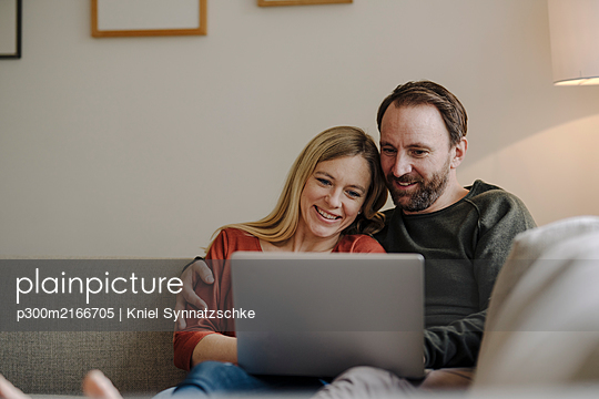 Couple sitting at home on couch, using laptop - p300m2166705 by Kniel Synnatzschke