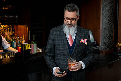 Stylish hipster businessman in suit drinking cocktail and checking smart phone in bar - p1192m2047223 by Hero Images