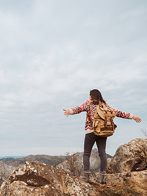 Woman with backpack, geometric patterned sweater and open arms on top of the mountain - p1522m2082750 by Almag