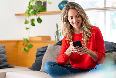 Smiling blond woman text messaging on mobile phone while sitting in living room at home - p300m2276567 by Steve Brookland