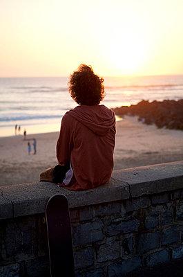 France, Aquitaine, Capbreton, skateboarder watching the sea at twilight - p300m975132f by Anita Fuchs