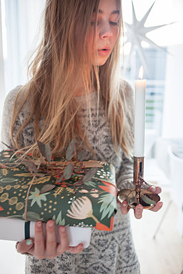 Girl holding Christmas gifts and candle - p312m1471894 by Christina Strehlow