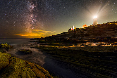 Milky way over lighthouse and rocky coast - p343m1475839 by Adam Woodworth