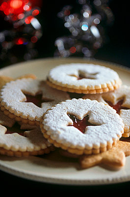 Plate of christmas party biscuits with a star stamp dusted with icing sugar - p3490577 by Jan Baldwin