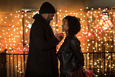 Romantic couple handing christmas gifts at night, New York, USA - p924m1230247 by Steve Prezant