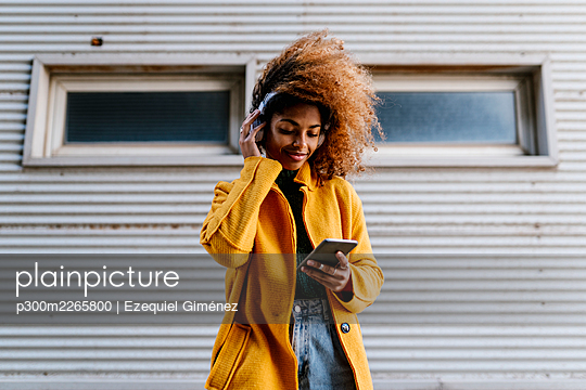 Smiling Afro woman using mobile phone while listening music through headphones against wall - p300m2265800 by Ezequiel Giménez